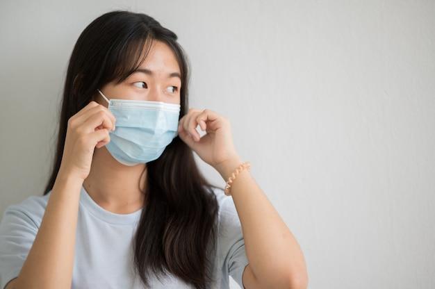 Ritratto del viso del primo piano studenti asiatici universitari femminili indossano una maschera e mantengono le distanze sociali durante l'orario scolastico.