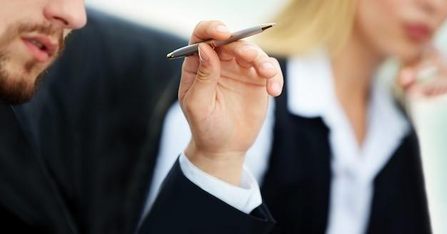 Fronte del primo piano di una mano di uomo d'affari serio con una penna in mano sullo sfondo del team aziendale