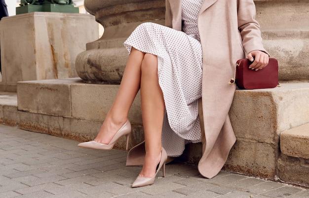 Le gambe della donna alla moda del primo piano indossano scarpe, vestito e seduta beige tacco alto abbigliamento autunnale e primaverile all'aperto