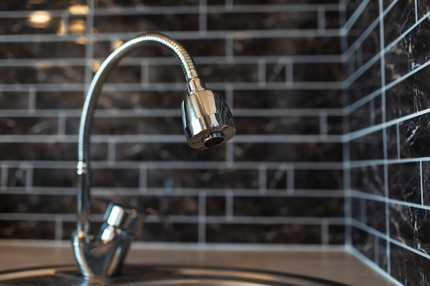 Primo piano del rubinetto nella zona cucina, sullo sfondo di un muro di mattoni scuri.
