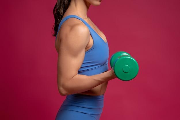 Primo piano del braccio femminile con manubri sulla parete marrone rossiccio