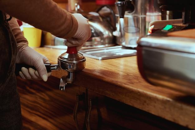 Primo piano delle mani del barista femminile tempera, premendo il caffè macinato in portafilter in metallo. pigiatura del caffè