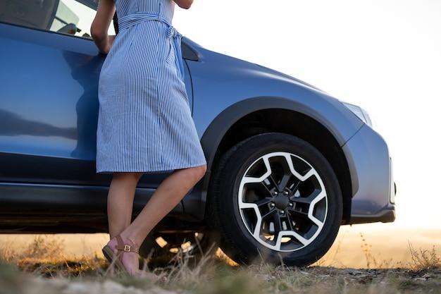 Primo piano dell'autista femminile che riposa vicino alla sua auto godendosi la vista del tramonto della natura estiva. destinazioni di viaggio e concetto di ricreazione.