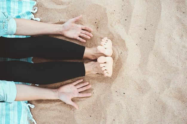 Primo piano dei piedi e delle palme femminili sulla sabbia con lo spazio della copia