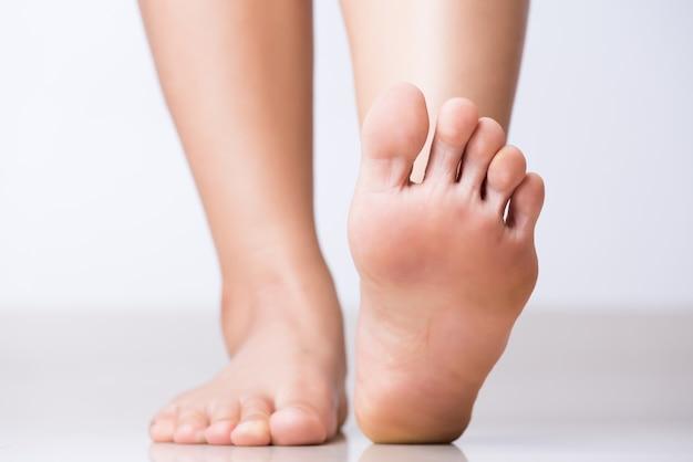 Dolore al piede femminile del primo piano, concetto di sanità