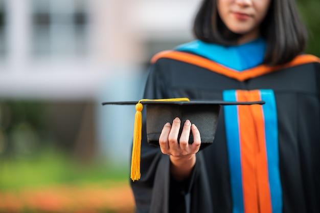 Primo piano di donne laureate, laureate, in possesso di un cappello nero