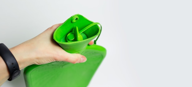 Primo piano della mano femminile che tiene la bottiglia di acqua calda medica verde e il cappuccio isolati su fondo bianco con lo spazio della copia.
