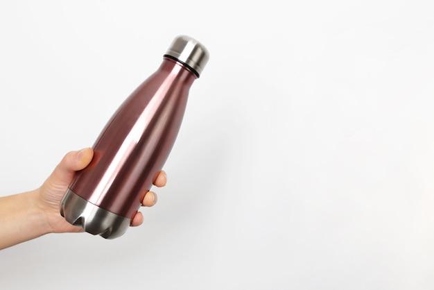 Primo piano della mano femminile, che tiene la bottiglia di acqua termica eco in acciaio inox riutilizzabile con mockup