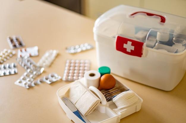 Mano femminile del primo piano che dispone il rifornimento di emergenza dell'organizzazione di stoccaggio del kit di pronto soccorso domestico del medicamento