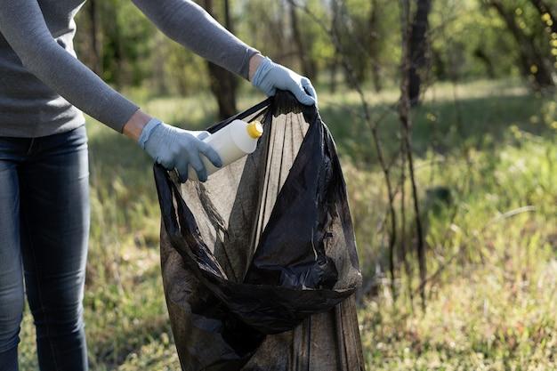 La mano femminile del primo piano che indossa un guanto di gomma getta una bottiglia di plastica in un sacchetto della spazzatura. il volontario rimuove la spazzatura. inquinamento ambientale.