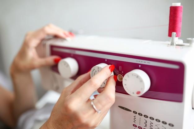 Primo piano delle mani femminili regolare il relè sulla manutenzione dell'attrezzatura della macchina per cucire