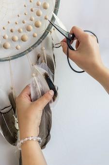 Mani femminili del primo piano che creano un acchiappasogni dell'amuleto della cultura tribale tradizionale con piume isolate