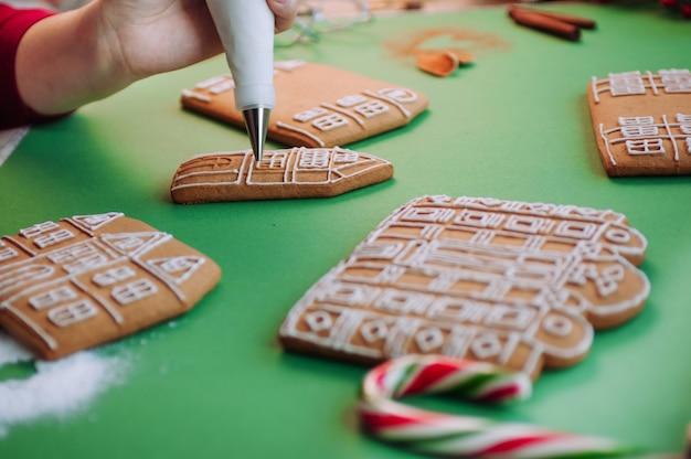 Primo piano delle mani femminili che decorano la casa dei biscotti del pan di zenzero di natale con il sacchetto di glassa messa a fuoco selettiva sulla borsa.