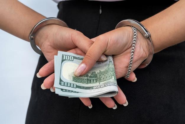 Primo piano delle mani femminili in manette e tenere banconote in dollari isolate su grigio. concetto di corruzione e tangente