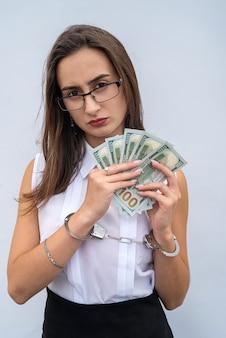 Primo piano delle mani femminili in manette e tenere banconote in dollari isolate su grigio. concetto di corruzione e tangenti