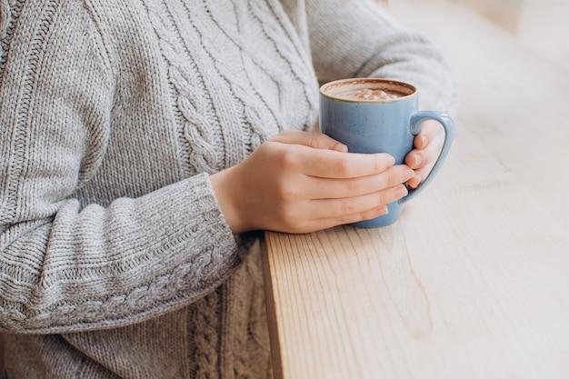 Primo piano le mani femminili tengono una tazza blu di cacao autunno capodanno e concetto di vacanza