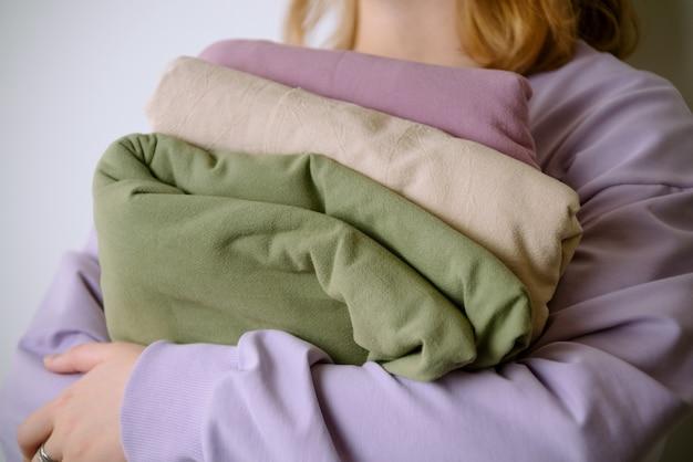 Primo piano delle mani femminili che tengono bei tessuti di cotone colorati pastello
