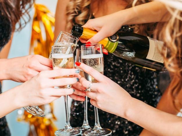 Primo piano delle mani femminili che tengono i vetri, ragazza che versa champagne da bere al suo compleanno con gli amici.