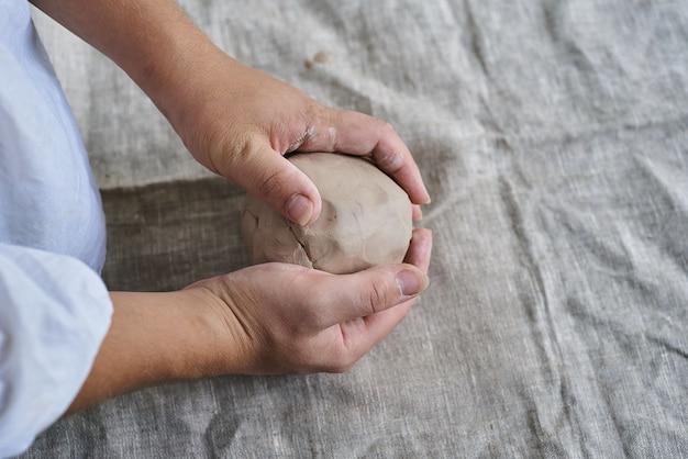 Mani femminili del primo piano che impastano un pezzo di argilla sulla tavola