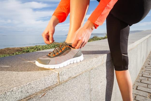 Primo piano delle mani femminili che legano i lacci delle scarpe da corsa sul muro prima di iniziare l'allenamento all'aperto