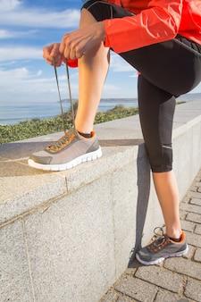 Primo piano delle mani femminili che legano i lacci delle scarpe da corsa