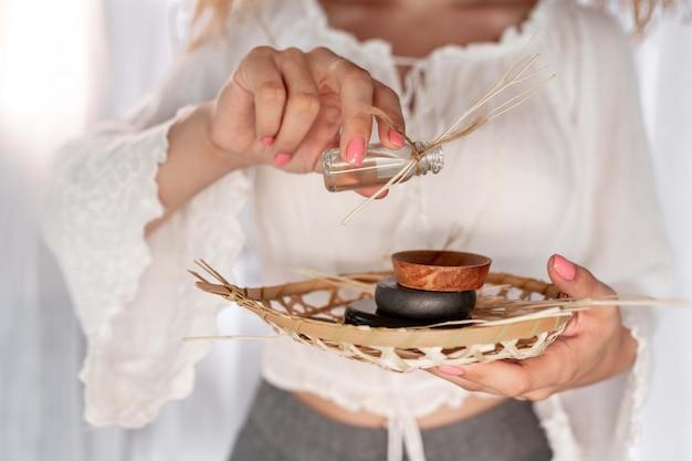 Primo piano: mani femminili con delicata manicure rosa versano olio in un piattino per fare un massaggio. massaggio tailandese con pietre. spa e cura