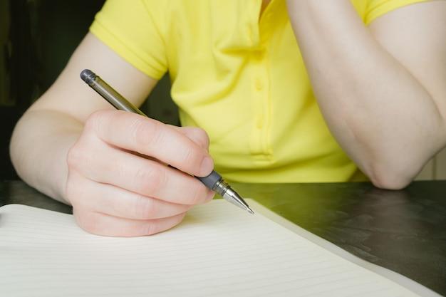 Primo piano delle mani femminili con penna e blocco note. la donna prende appunti nella cartella di lavoro. lo studente si prepara per gli appunti delle lezioni.