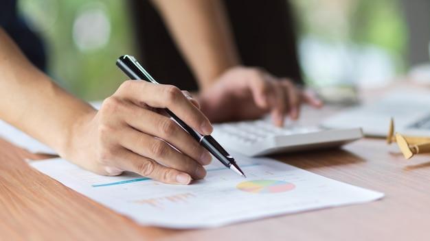 Primo piano della scrittura femminile sul rapporto finanziario durante il calcolo in ufficio