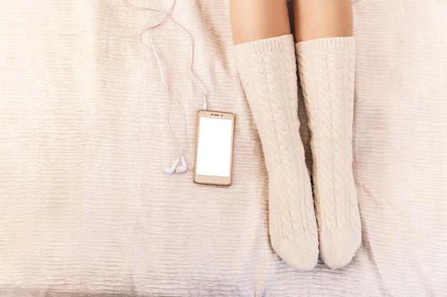 Primo piano delle gambe femminili in calzini rosa accanto a un telefono cellulare
