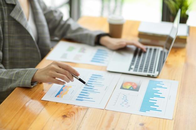 Primo piano, responsabile femminile che controlla i dati di vendita di affari sui documenti. laptop e relazione sulla scrivania, penna che punta su documenti
