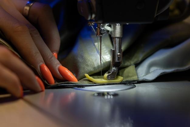 Il primo piano della sarta o del progettista femminile cuce sulla produzione dell'industria del cucito della macchina da cucire