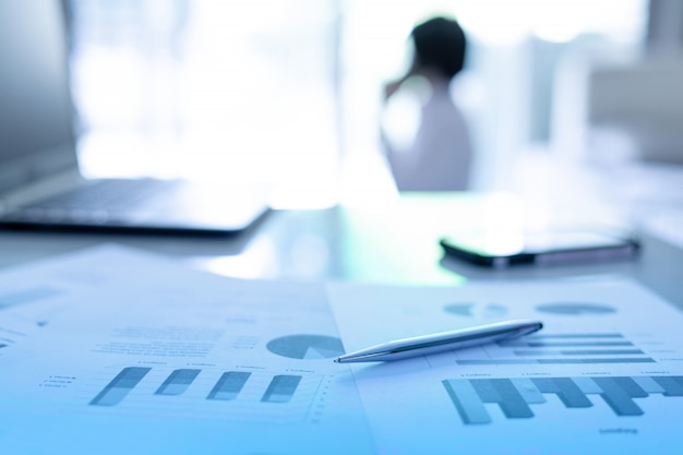 Primo piano del documento finanziario con la penna e il computer portatile sullo scrittorio all'ufficio e l'uomo di affari che parla al telefono