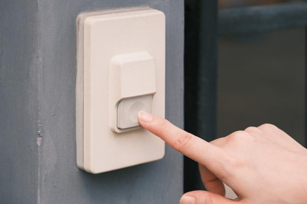 Primo piano dito della mano della donna sta premendo un pulsante campanello o cicalino a casa