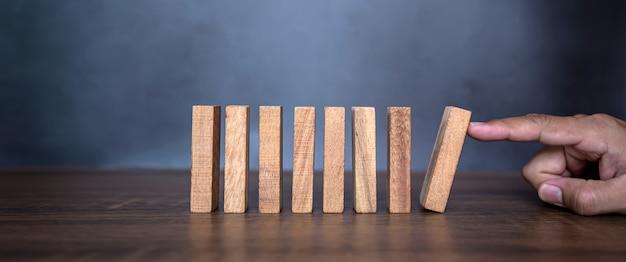 Le dita del primo piano impediscono al gioco del crollo del blocco di legno di cadere nel domino