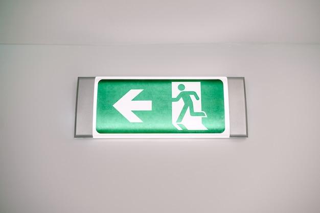 Primo piano di un segno di luce di evacuazione di sicurezza antincendio con un uomo che corre e una freccia sul muro