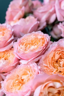 Primo piano fiori in mano fiorista donna sul posto di lavoro disponendo un bouquet con rose crisantemo carnati...