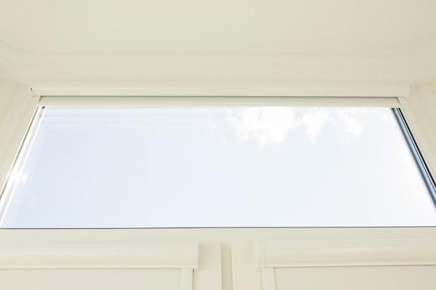 Frammento di primo piano della finestra in una stanza su uno sfondo di cielo blu