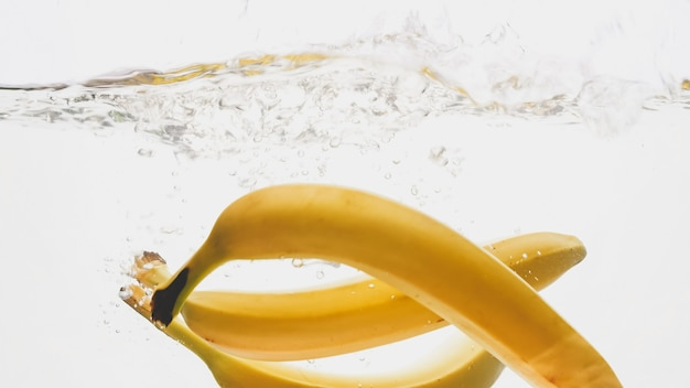 Primo piano di banane gialle mature fresche che cadono e si spruzzano in acqua chiara