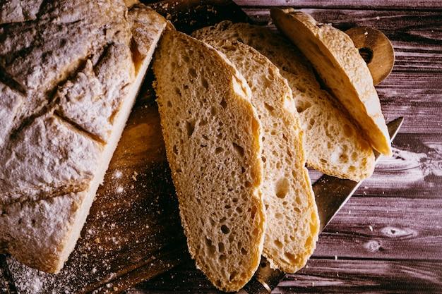 Primo piano di fette di pane fatto in casa appena tagliate su un tagliere con un coltello su un tavolo