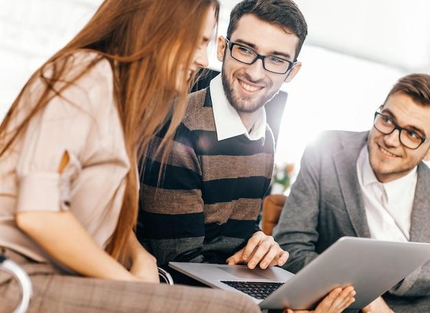 Primo piano del team aziendale amichevole che lavora al computer portatile e discute di questioni aziendali.