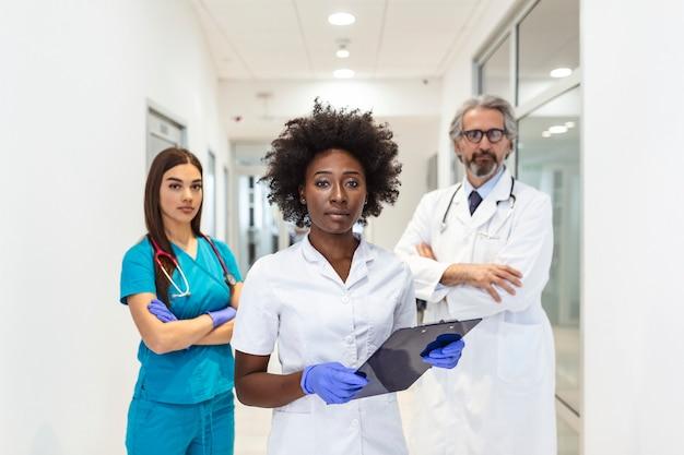 Primo piano vista frontale di un gruppo di medici e infermieri di età mista in piedi fianco a fianco e guardando la telecamera.