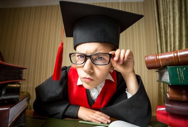 Ritratto divertente del primo piano della ragazza astuta in protezione e occhiali di graduazione che esaminano macchina fotografica