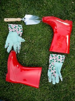 Guanti da giardino del primo piano, vanga e stivali di gomma rossi che si trovano sull'erba verde