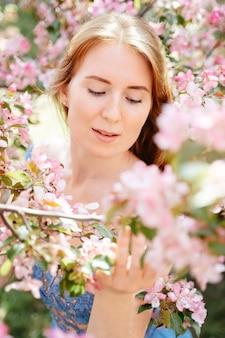Ritratto delicato del primo piano di una ragazza dai capelli rossi intorno ai suoi fiori rosa da un ciliegio e da una mela...