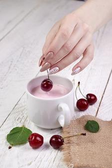 Le mani della ragazza del primo piano tengono la ciliegia fresca sul vetro con yogurt, tavolo in legno chiaro. gustosa colazione e un ottimo inizio di giornata