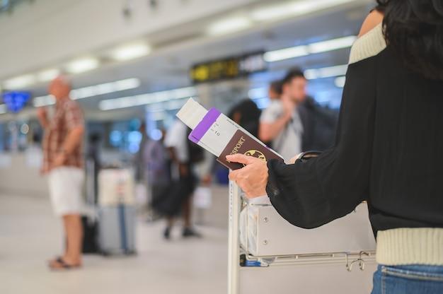 Primo piano dei passaporti della holding della ragazza e della carta d'imbarco all'aeroporto