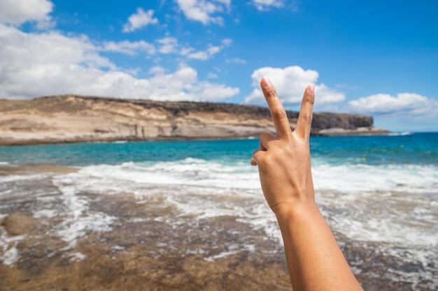 Primo piano di una mano di ragazze che fa il segno v è in spiaggia a godersi l'estate gesto della mano per concetti di felicità e divertimento and