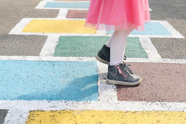 Primo piano delle gambe delle ragazze in un vestito rosa e campana disegnata su asfalto bambino che gioca a campana