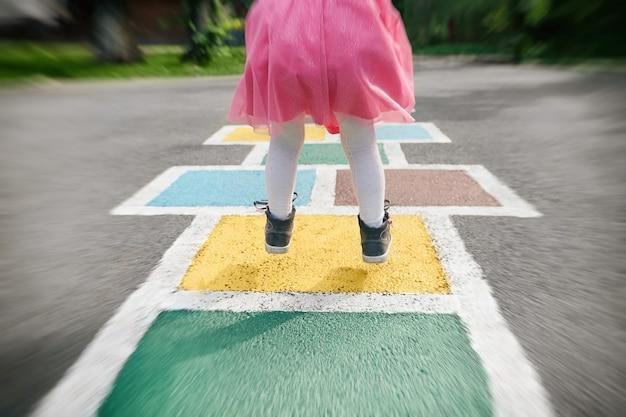 Primo piano delle gambe delle ragazze in un vestito rosa e campana disegnata su asfalto bambino che gioca nel parco giochi