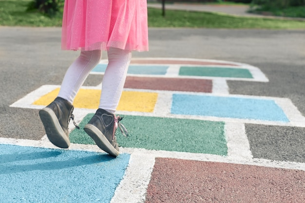 Primo piano delle gambe delle ragazze con un vestito rosa e una campana disegnata su attività all'aperto sull'asfalto